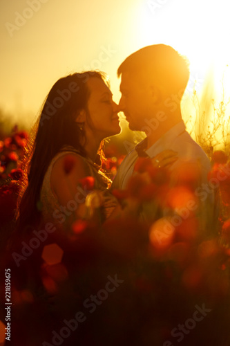 Fotografia  man and woman in poppy field at sunset, romance