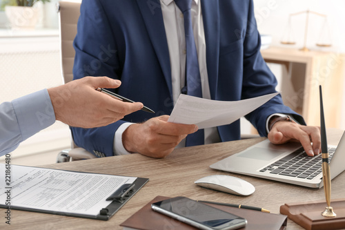 Leinwand Poster Lawyer working with client at table in office, focus on hands