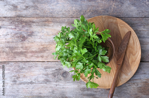 Flat lay composition with fresh green parsley and space for text on wooden background