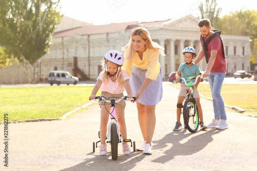 Happy parents teaching children to ride bicycles outdoors