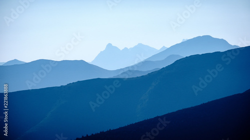 Foto op Aluminium Nachtblauw mountain top panorama in autumn covered in mist or clouds