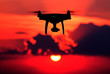 canvas print picture - Silhouette of a radio-controlled drone against a red sky. An unmanned aerial vehicle at sunset. The concept of digitalization and video surveillance.