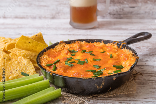 Foto op Aluminium Buffel Baked cheese dip with chips, celery and beer