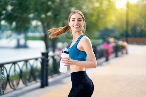 Foto  Happy woman with bottle of water, during morning jogging