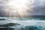 Rays of sunlight break through storm clouds above the open ocean waves in a heavenly seascape