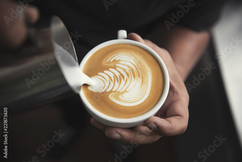 Barista making latte or Cappuccino art with frothy foam, coffee cup in cafe.
