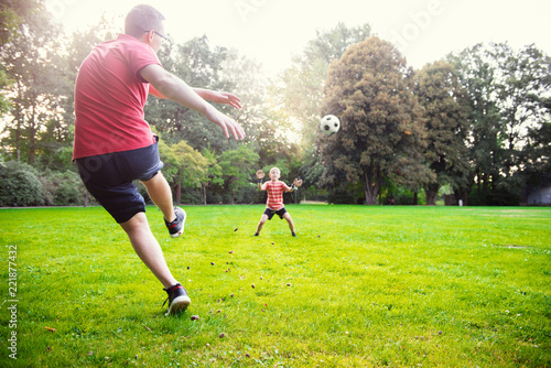 Happy young father play with his little son football in sunny park