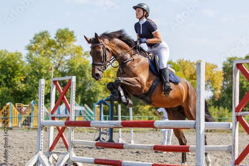 Young horse rider girl jumping over a hurdle on show jumping competition
