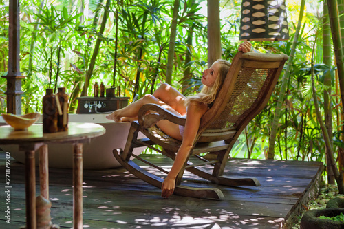 Valokuvatapetti Young girl in underwear recline and relax at wooden rocking armchair