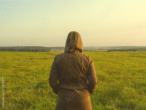 Girl in a windbreaker stands back in the field in autumn Wallpaper Mural