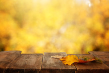 Image Of Front Rustic Wood Table With Dry Gold Leaves And Fall Bokeh Background.