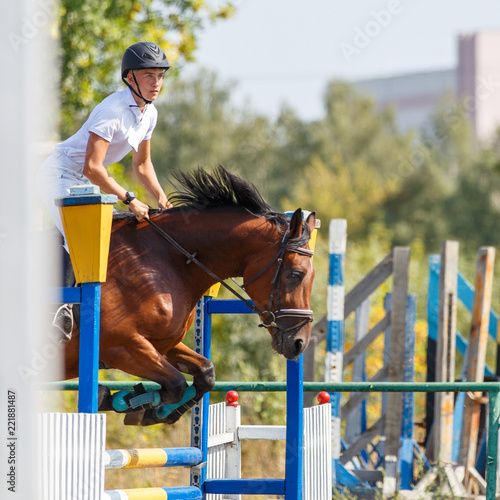 Fotografija Young man riding horse on show jumping event