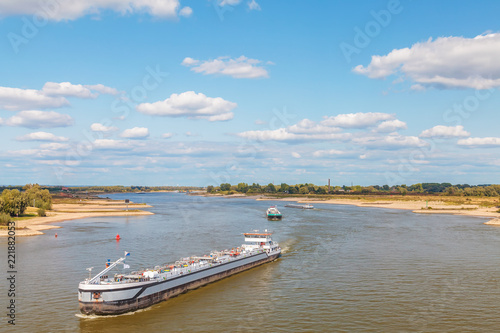 The Dutch Waal river near Nijmegen with cargo ships passing by