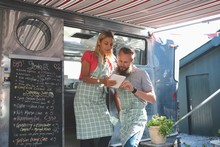 Couple Using Digital Tablet In Food Truck