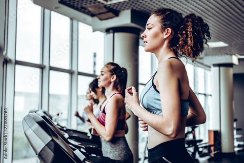 Photo sur Toile Fitness Beautiful group of young women friends exercising on a treadmill at the bright modern gym