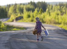 Caucasian Girl Child Walking Away With A Bear And Suitcase. Curvy Road. Concept Image Of A Runaway Child.