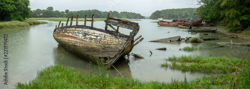 Panorama sur des épaves de bateaux dans un cimetière marin dans le bras d'une rivière sous la pluie