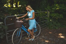 Woman Standing With Bicycle In The Park