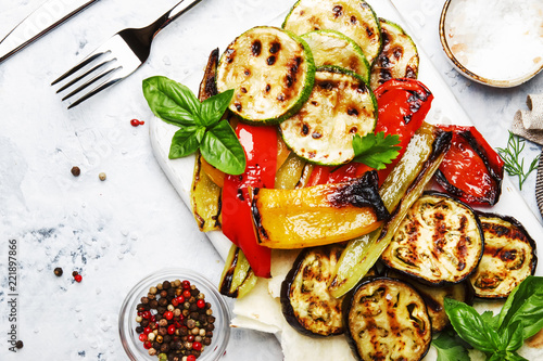 Fototapeta Grilled colorful vegetables, aubergines, zucchini, pepper with spice and green basil on serving board on white background, top view obraz