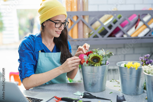 Portrait of smiling contemporary woman arranging flower compositions and using laptop in shop, copy space