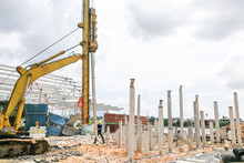 Worker Carrying Out Ground Piling Work At Construction Site