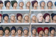 Woolen Hats On The Silvery Heads Of The Mannequins In The Store. A Variety Of Female Winter Knitted Hats On Mannequin Heads