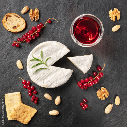 An overhead photo of Camembert cheese with a glass of red wine, fruits and nuts, shot from above on a black background with copy space