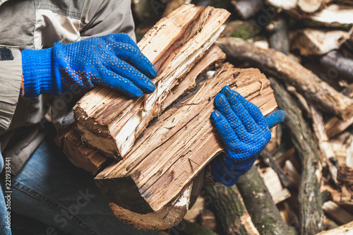 Foto Hands in gloves hold wooden logs