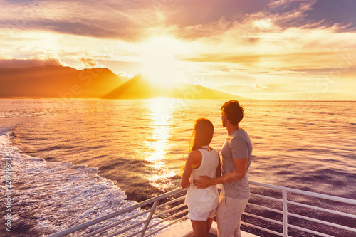 Travel cruise ship couple on sunset cruise in Hawaii holiday. Two tourists lovers on honeymoon travel enjoying summer vacation.