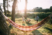 Young Sympathetic Family - Mom, Dad And Son Rest In Nature, Near A Hammock