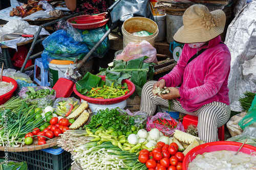 Vietnamese produce vendor selling fresh vegetables in a traditional market in Hue, Vietnam