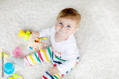Obraz Adorable baby girl playing with educational toys in nursery. Happy healthy child having fun with colorful different toys at home. Baby development and first steps, learning to play and to grab. - fototapety do salonu
