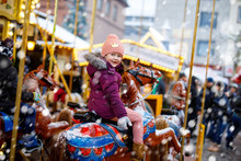 Adorable Little Kid Girl Riding On A Merry Go Round Carousel Horse At Christmas Funfair Or Market, Outdoors. Happy Child Having Fun On Traditional Family Xmas Market In Dresden, Germany