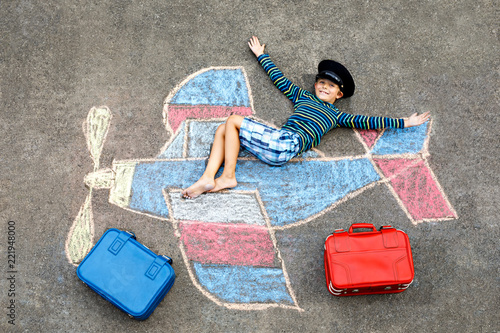 Fotografiet  Little kid boy having fun with with airplane picture drawing with colorful chalks on asphalt