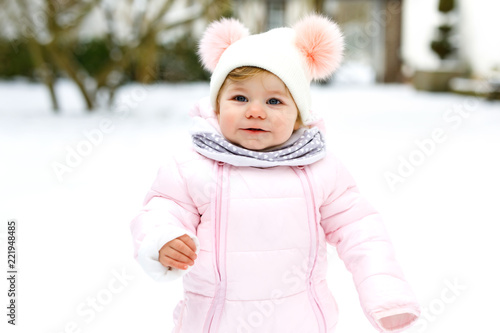 22a6fc05c2ba Adorable little baby girl making first steps outdoors in winter ...