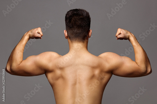 Tuinposter Akt man with muscular body and strong back of bodybuilder athlete with biceps and triceps on grey background, sport and training