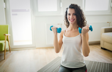 Fototapeta Young attractive sportswoman doing exercises at home