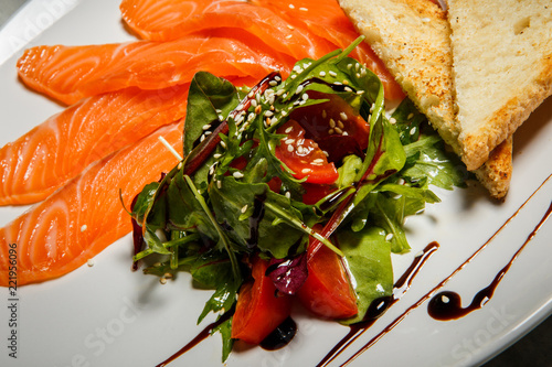 Fotografia  closeup rucola and tomato salad served with salmon slices and toasted bread