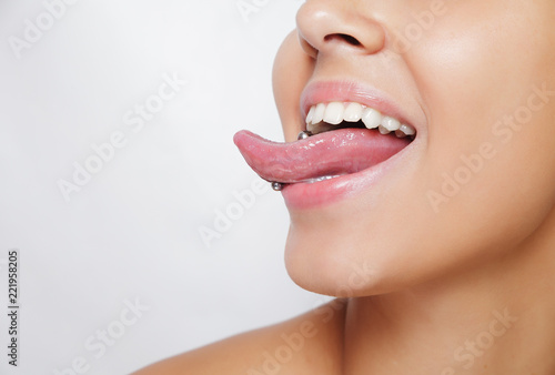 Fotografia, Obraz Beautiful woman sticking out her tongue and showing her young piercing