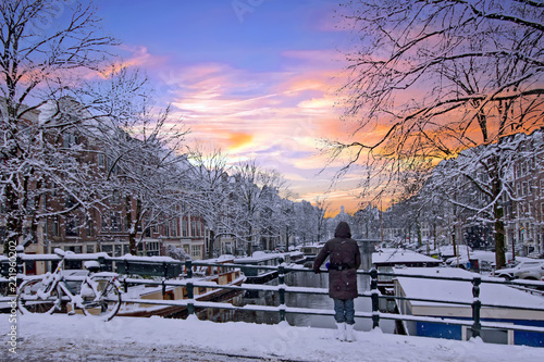 Amsterdam covered with snow  in winter in the Netherlands at sunset Canvas-taulu