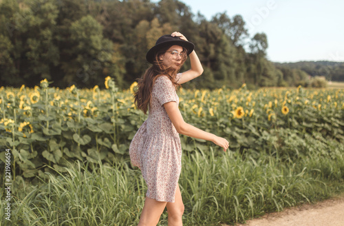 Young brunette girl with a hat and glasses posing and walking in the middle of a countryside of sunflowers