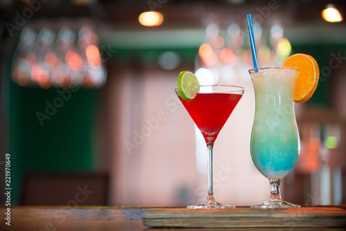 Photo  Cosmopolitan and Blue Hawaiian cocktails on the bar counter, blue and red drinks