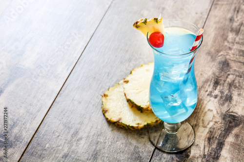 Blue Hawaiian cocktail on wooden table. Copyspace