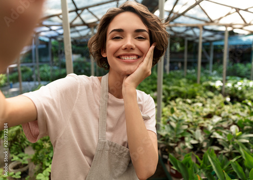 Gardener standing over plants in greenhouse take a selfie by camera.