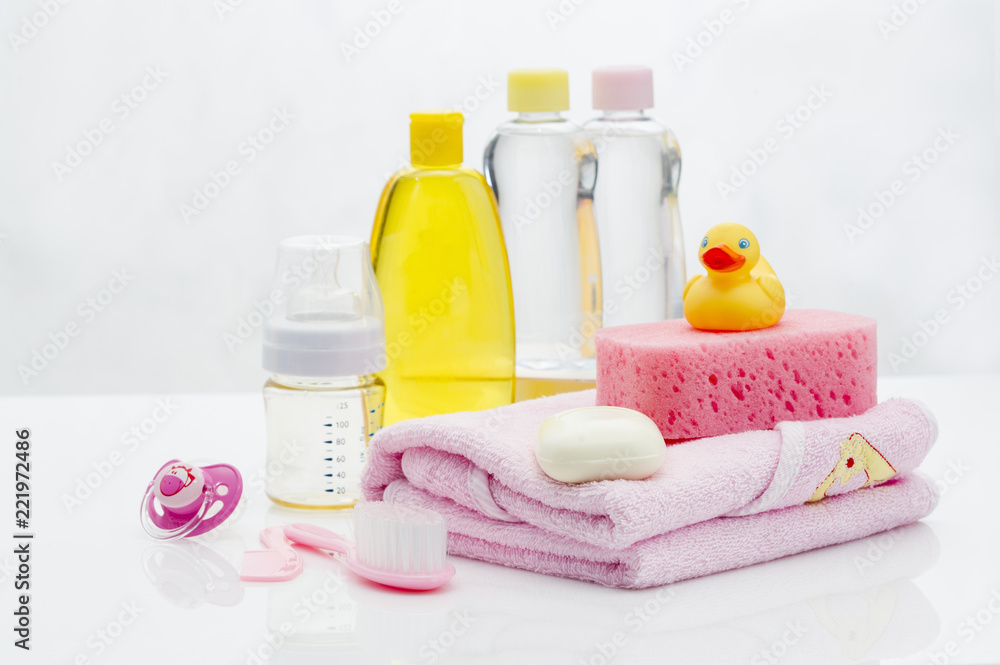 Fototapeta Still life with babt hygiene and bath items, shampoo bottle, essential oil, baby soap, towel, pacifier, rubber toy, shower puff