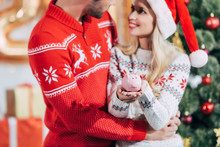 Couple In Santa Hats Holding P...