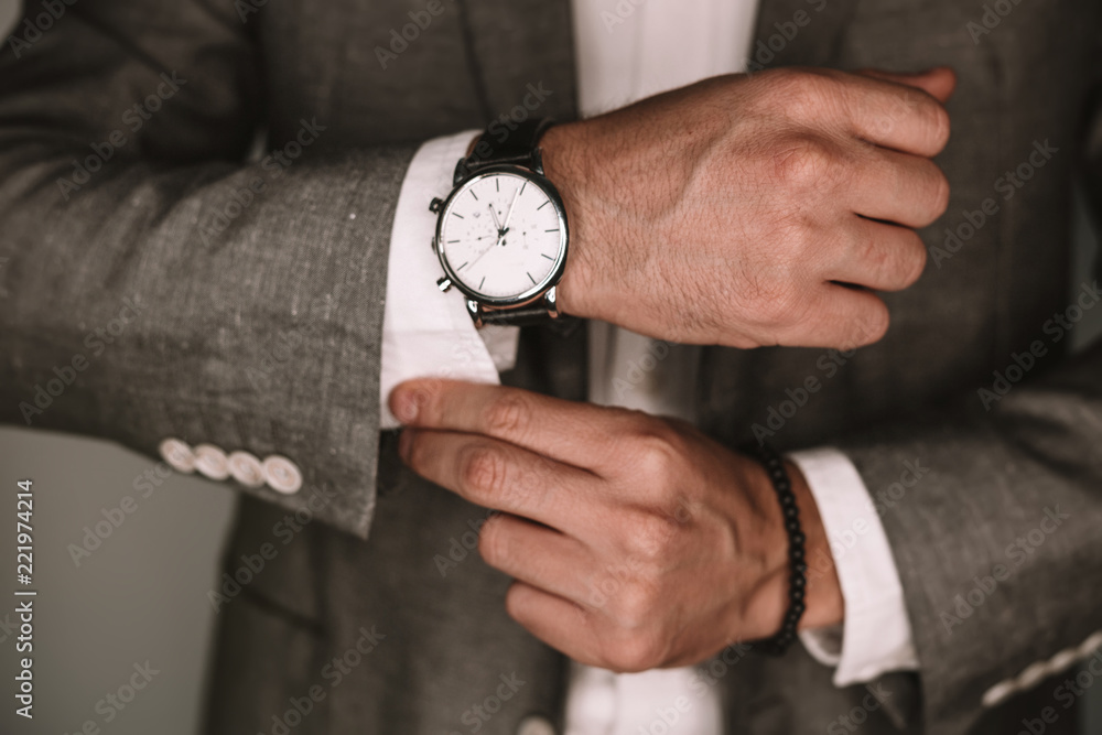 Fototapeta closeup fashion image of luxury watch on wrist of man.body detail of a business man.Man's hand in a grey shirt with cufflinks. Tonal correction