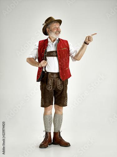 Portrait of Oktoberfest senior man in hat, wearing a traditional Bavarian clothes standing at full-length at studio Fototapeta