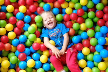 Fototapeta na wymiar Laughing child in a game pool with colorful balls
