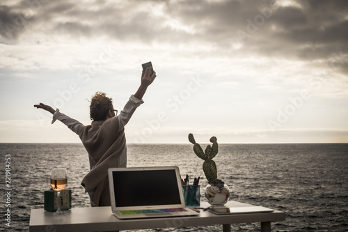 Happy lady working outdoor near the ocean in an alternative free office without walls and limits Wallpaper Mural